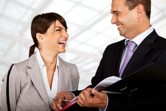 We did great again. Two business people wearing suits are laughing over files royalty free stock photos