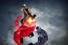 We did it. Hand of winner tighten the cup against blue sky background Stock Photography