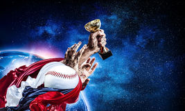 We did it. Hand of winner tighten the cup against blue sky background. Elements of this image are furnished by nASA Royalty Free Stock Photos
