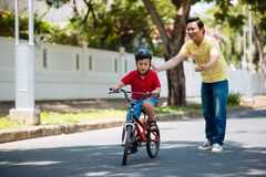 He did it. Happy father looking at his son riding a bike Stock Photos