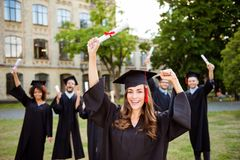 We did it! Happy grad girl is smiling, group of her friends clas. S mates are behind. She is in a black mortar board, with red tassel, in gown, with nice brown Stock Image