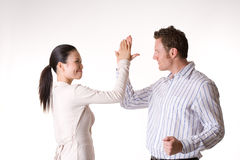 We did it high five. Asian business woman and Caucasian man high five after a success Stock Photo