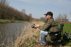 Did I catch anything?. Man sitting in his fishing chair reeling in Stock Photo