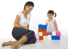 We did it mom!. Happy mother sitting on the floor with daughter in front of colored blocks. White background Royalty Free Stock Photos