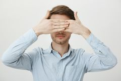 Did not see so did not happen. Portrait of calm relaxed young man with bristle covering eyes with both palms, standing. In ordinary blue shirt against gray Royalty Free Stock Images