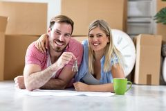 We did it, success couple holding keys  at there new apartment. We did it, success smiling couple holding keys at there new apartment Stock Photos