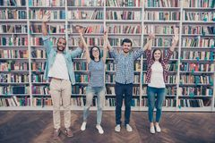 We did it together! Conception of successful teambuilding. Four. Happy international students putting their hands up together, wearing casual outfits, standing Stock Photography