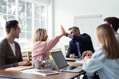 We did it! Two cheerful young business people giving high-five while their colleagues looking at them and smiling. We did it! Two cheerful young business people royalty free stock photo