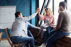 We did it! Two cheerful young business people giving high-five while their colleagues looking at them and smiling. We did it! Two cheerful young business people stock photo