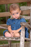 Did You Do that???. A cute little girl sitting in an old rocker clasping her hands outdoors wearing a denim outfit trimmed in leopard print Royalty Free Stock Images