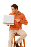 Did you see this. Portrait of a mature adult man wearing an orange sweater and khakis sitting on a stool pointing to the screen on a laptop computer looking at royalty free stock images