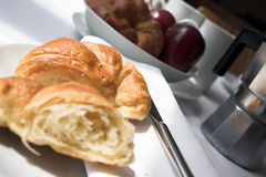 Did you start without me..?. Half eaten croissant - croissants, fruit & coffee in background Royalty Free Stock Photos