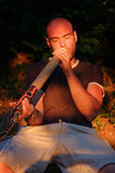 Didgeridoo player. Young guy play on didgeridoo with the australian aboriginal musical instrument in lights of sunset Royalty Free Stock Images