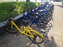 Didi y OFO compartieron las bicis en el lado del camino en el reparto del tiempo del día es muy populares adentro fotografía de archivo
