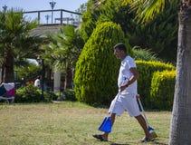 DIDIM, DIE TÜRKEI - 9. JULI 2014 Hotelreiniger kommt mit Werkzeugen für den Rasen Lizenzfreie Stockfotos