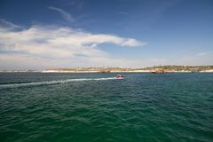 DIDIM, TURKEY – SEPTEMBER 6, 2016-A high-speed motor boat with a couple of people aboard quickly rushes through the sea. DIDIM, TURKEY – SEPTEMBER 6 Royalty Free Stock Photography