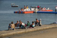 DIDIM, TURKEY – SEPTEMBER 4, 2016- The local population and tourists sunbathe sitting on the pontoon. And the embankment of the Turkish town of Didim Royalty Free Stock Image