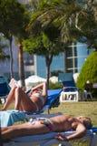 DIDIM, TURQUÍA - 9 DE JULIO DE 2014 Veraneantes que toman el sol en la playa del césped Foto de archivo libre de regalías