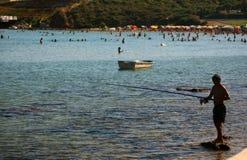 DIDIM, TURQUIA - 9 DE JULHO DE 2014 Pescador com uma pesca da vara de pesca no mar Fotos de Stock