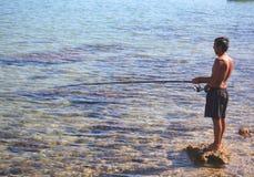 DIDIM, TURQUIA - 9 DE JULHO DE 2014 Pescador com uma pesca da vara de pesca no mar Imagens de Stock Royalty Free