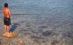 DIDIM, TURQUIA - 9 DE JULHO DE 2014 Pescador com uma pesca da vara de pesca no mar Foto de Stock