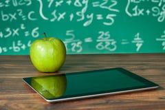 Didital minnestavla och äpple på skrivbordet Royaltyfri Fotografi