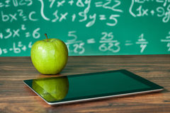 Didital tablet and apple on the desk Royalty Free Stock Photography