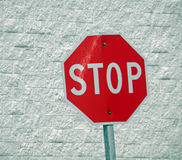 Almost Didn't. A photograph of a scratched and dented stop sign Stock Image