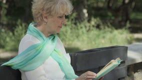 Die ältere Frau, die auf Bank sitzt, liest ein Buch im Park stock footage