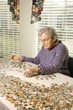 Die ältere Frau, die Spannvorrichtung tut, sah Puzzlespiel stockbild
