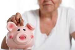Die ältere Frau, die Stiftgeld steckt, prägt in rosa piggybank Schlitz Stockbild