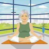 Die ältere Frau, die Yoga tut, trainiert im Lotussitz, der auf Matte sitzt Stockbild