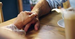 Die ältere Frau, die ihre Hand auf älteres setzt, bemannt Hand im Café 4k stock video footage