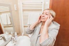 Die ältere Frau, die ihre weiche Gesichtshaut berührt und tut die Massage und zu Hause schaut im Spiegel lizenzfreies stockfoto