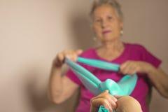 Die ältere Frau, die Rehabilitation tut, trainiert mit elastischem Band Lizenzfreie Stockfotos