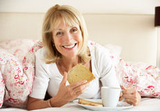 Die ältere Frau Snuggled unter Duvet Frühstück essend lizenzfreies stockfoto