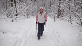Die ältere Frau verbringt die Freizeit im Holz Der Winterwald stützt das Niveau des körperlichen activit stock footage