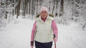 Die ältere Frau verbringt Freizeit im Holz Winterwald die Frau stützt das Niveau der körperlichen Tätigkeit E stock video