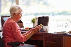 Die ältere setzende Frau wird in Kasten Lizenzfreies Stockbild