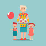 Die ältere vorbereitete Frau backt für ihre Enkelkinder zusammen Stockfoto