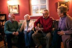 Die älteren Leute, welche die lächelnde Partei machen und genießen zusammen zu Hause lizenzfreie stockfotos