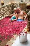 Die älteren Paare, die im Blumen-Blumenblatt sich entspannen, bedeckten Pool am Badekurort Lizenzfreies Stockbild