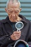 Die älteren Personen, zum mit einem Vergrößerungsglas zu lesen Stockfotografie