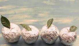 Die Äpfel der Fahne vier, die in der Folie eingewickelt werden, sind natürliche grüne Blätter Stockbilder