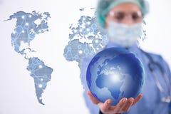 Die Ärztin, die Erde im Globalisierungskonzept hält Lizenzfreie Stockbilder