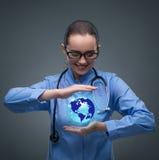 Die Ärztin, die Erde im Globalisierungskonzept hält Lizenzfreie Stockfotos