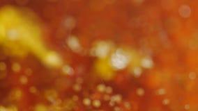 Die Ölblasen, die auf Oberflächenwasser schwimmen, ist in der Bewegung mit rotem Hintergrund stock video footage