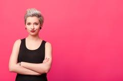 Die überzeugte Frau, die mit den Armen steht, kreuzte über rosa Hintergrund Lizenzfreie Stockfotografie