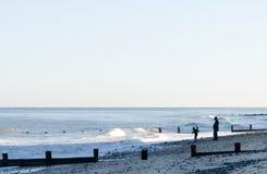 Die Abbildungen, die an einem Abend silhouettiert werden, setzen in England auf den Strand. Lizenzfreie Stockfotografie