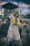 Die Abendvorstellung Eine gruselige Frauenfigur in einer Gasmaske mit einem Buch um ihren Hals und einen drastischen Himmel Lizenzfreie Stockfotos